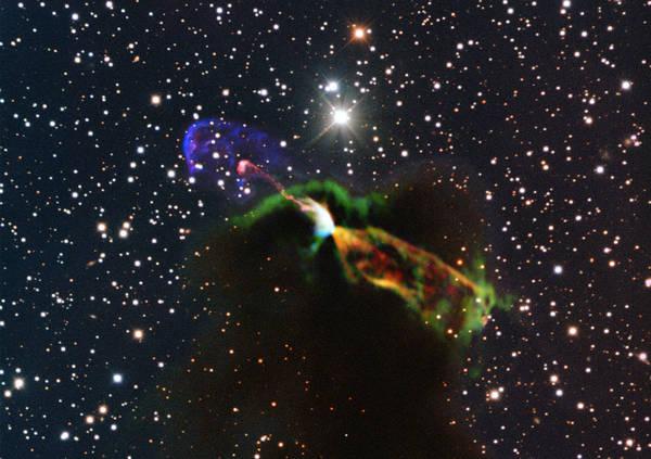 Le osservazioni della stella appena nata fatte dal telescopio Alma (in arancio e verde, in basso a destra) rivelano un grande getto energetico in allontanamento. A sinistra (in rosa e viola) la parte visibile del getto direto verso la Terra